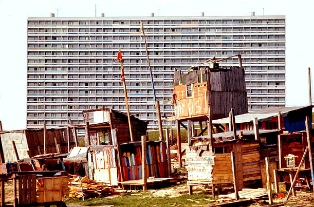 Høje Gladsaxe in front of the sterile highraised blocks. Copenhagen - 1975. The Ratfree House - built by boys on high stilts, in the foreground. 1975